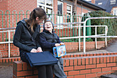 Teenage sister with young brother at primary school
