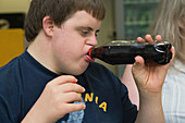 Teenage boy with Down Syndrome drinking a bottle of cola