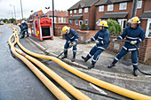 Members of the fire rescue service moving high volume pumps