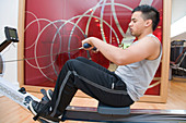 Young man using a rowing machine at gym