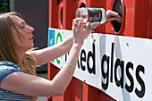 Woman recycling glass at bottle bank at city tip