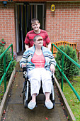 Young carer pushing his mother in a wheelchair