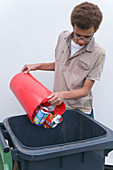 Teenage boy putting tins and cans into recycling wheelie bin