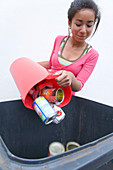Teenage girl putting tins and cans into recycling bin