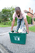 Man placing curb side recycling collection box on pavement