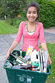 Teenage girl carrying curb side recycling collection box