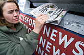 Woman putting old newspaper into a recycling bank