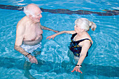 Two older people having a chat in a swimming pool