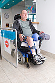 Male wheelchair user going through controlled access gate