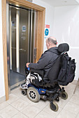 Male wheelchair user entering a lift