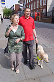 Vision impaired man with guide dog and sighted guide
