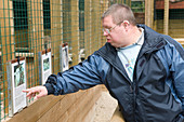 Man with learning disabilities reading sign on a bird cage