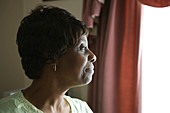 Portrait of an older woman looking out of a window