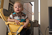 Boy at home in high chair