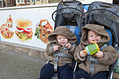 Twins in buggy outside chip shop