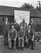 ICI powder works team in front of Safety League board, 1962