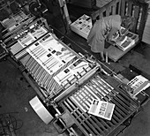 Stacking finished brochures at a printers, 1959