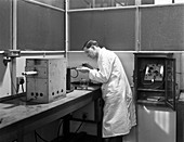 Lab technician using a table top test furnace, 1962