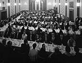 Guests seated before dinner at a social evening, 1963