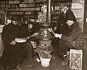 A group of men around a stove in a shop, USA, c1910