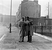 Two Afro-Caribbean men reading a map in the street, London.