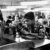 Woman working at a sewing machine, London