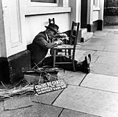Man mending a chair on an East End street, London, 1950s