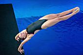 Diver in handstand on diving platform