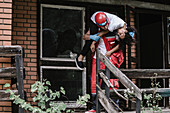 Rescue worker carrying woman out of damaged house