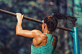 Woman exercising on horizontal bar outdoors