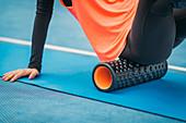 Female athlete using foam roller
