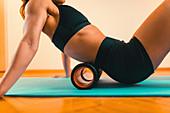 Massaging lower back with foam roller