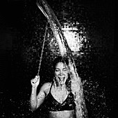 Woman taking a cold shower from ice bucket