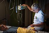 Nurse administering sedative on palliative care ward
