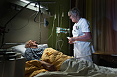 Nurse checking on patient on palliative care ward