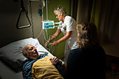 Nurse and daughter with patient on palliative care ward