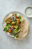 Wrap with tabbouleh and falafels, greek yoghurt, avocado, spinach and coriander