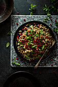 Middle eastern tabbouleh salad with bulgar wheat, parsley, mint, tomatoes and pomegranate seeds