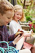 Kinder essen Muffins beim Picknick