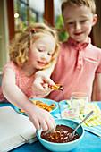 Kinder dippen Brezeln in Schokoladensauce
