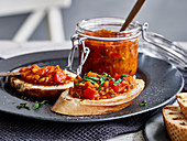 Homemade tomato chutney in a jar and on toasted bread slices