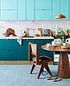 Küchenzeile in Blautönen, Tapete in Marmoroptik, runder Holztisch und Designerstuhl,