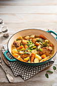 Spring casserole with chicken tights, new potatoes, baby carrots, young cabbage, broad beans and sage