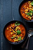 Spicy bean, corn and tomato chunky soup with chilli, cumin, . View from above.