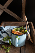 Tomato soup in a cup with wooden spoons