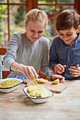 Kinder bereiten Kartoffelgratin zu
