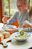 Kinder essen Hähnchen-Mais-Cremesuppe