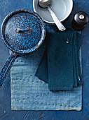 Blauer Stieltopf, Schüssel, Besteck und Stoffservietten