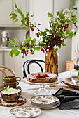 Branches of redcurrants in vase and cake on set table