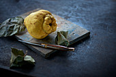 A quince on a wooden board with a knife